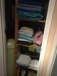 The airing cupboard with towels arranged from big to small, from bottom to top.